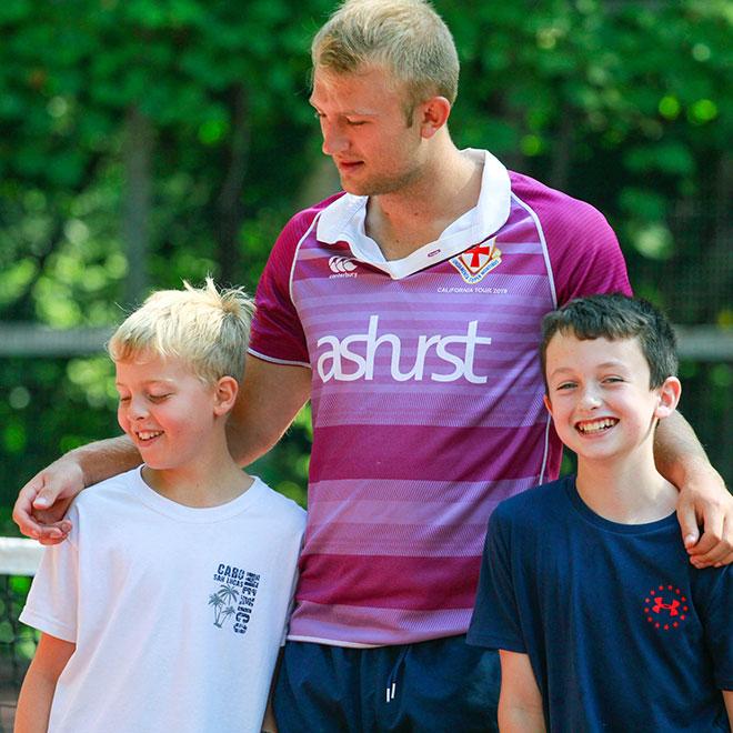 Summer camp staff helping kids
